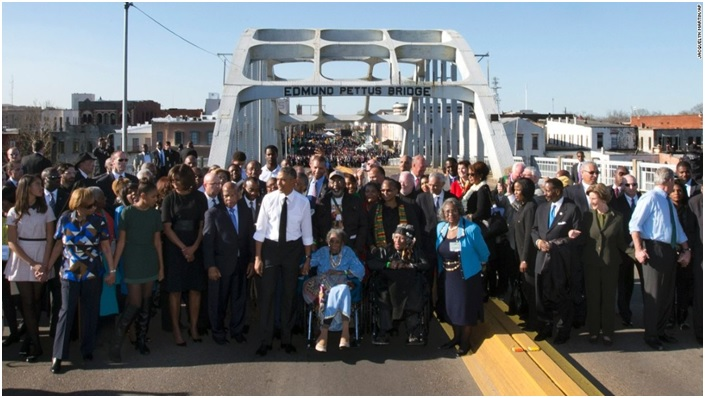 Photo courtesy of CNN President Barack Obama, First Lady Michelle Obama, daughters Malia and Sasha and several members of Congress, civil rights leaders and others made a symbolic walk across the Edmund Pettus Bridge on March 7.