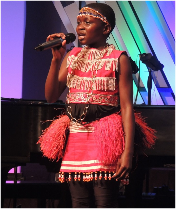 Photos by James Celeste  One of the Children of the  Mwangaza choir shared her testimony  to the audience.