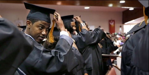 Photo courtesy of AP Photo/Mark Humphre In this May 5, 2014 photo, Krishaun Branch, left, moves the tassel on his mortarboard to the left side after gradu-ating from Fisk University in Nashville, Tenn.