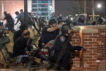 Photo courtesy of AP Photo/ St. Louis Post-Dispatch Laurie Skrivan Police take cover after two officers were shot while standing guard in front of the Ferguson police station on March 12.