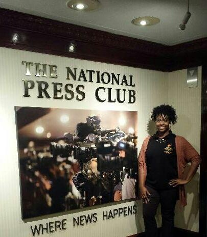 Dominique King posed in front of the National Press Club sign where she reported  during Black Press Week's various events.
