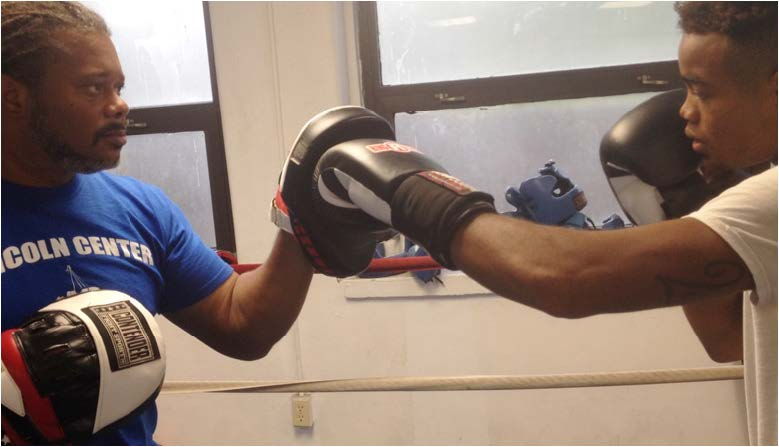 Amateur boxer Rashod Cooper (right) goes through a drill on the mitts with trainer Tyrese Williams at the Lincoln Neighborhood Boxing Club. Cooper Fights this Saturday at the National Guard Armory. Photo by St. Clair Murraine