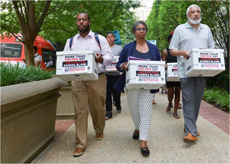 (Left-Right) Eugene Puryear of the Stop Police Terror Project in Washington, D.C., Lois Wilkins, the Freeland, Mich., resident and mother of four who started the petition on MoveOn.org, and Reverend Graylan Hagler, the senior pastor of the Plymouth Congregational United Church of Christ carried boxes of signed petitions to the visitor's entrance of the Department of Justice.  Photo Courtesy  of  Freddie Allen/NNPA News Wire