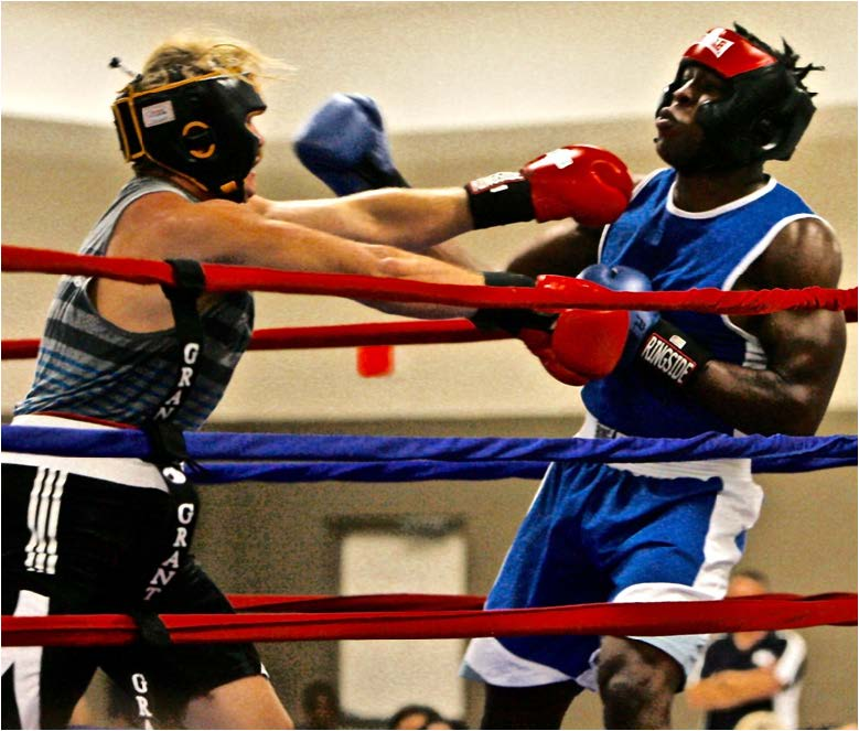 Robert Arnold (left) gets tagged with a right hand from Brandon Denmark of Tallahassee during their heavyweight boxing match at the National Guard Armor