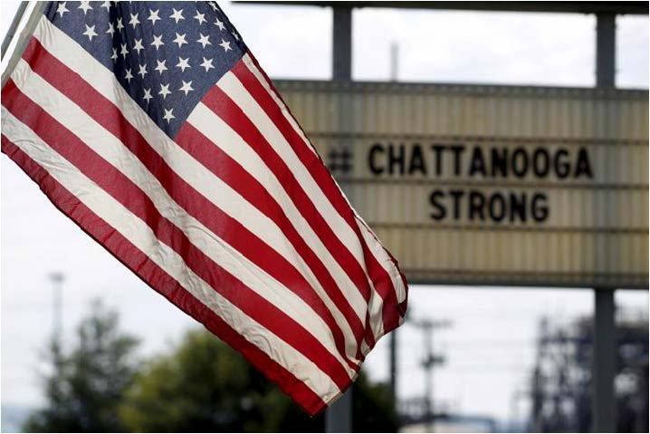 A U.S. flag flies near a sign in honor of the four Marines and one sailor  killed in Chattanooga, Tenn.  Reuters/Tami Chappell