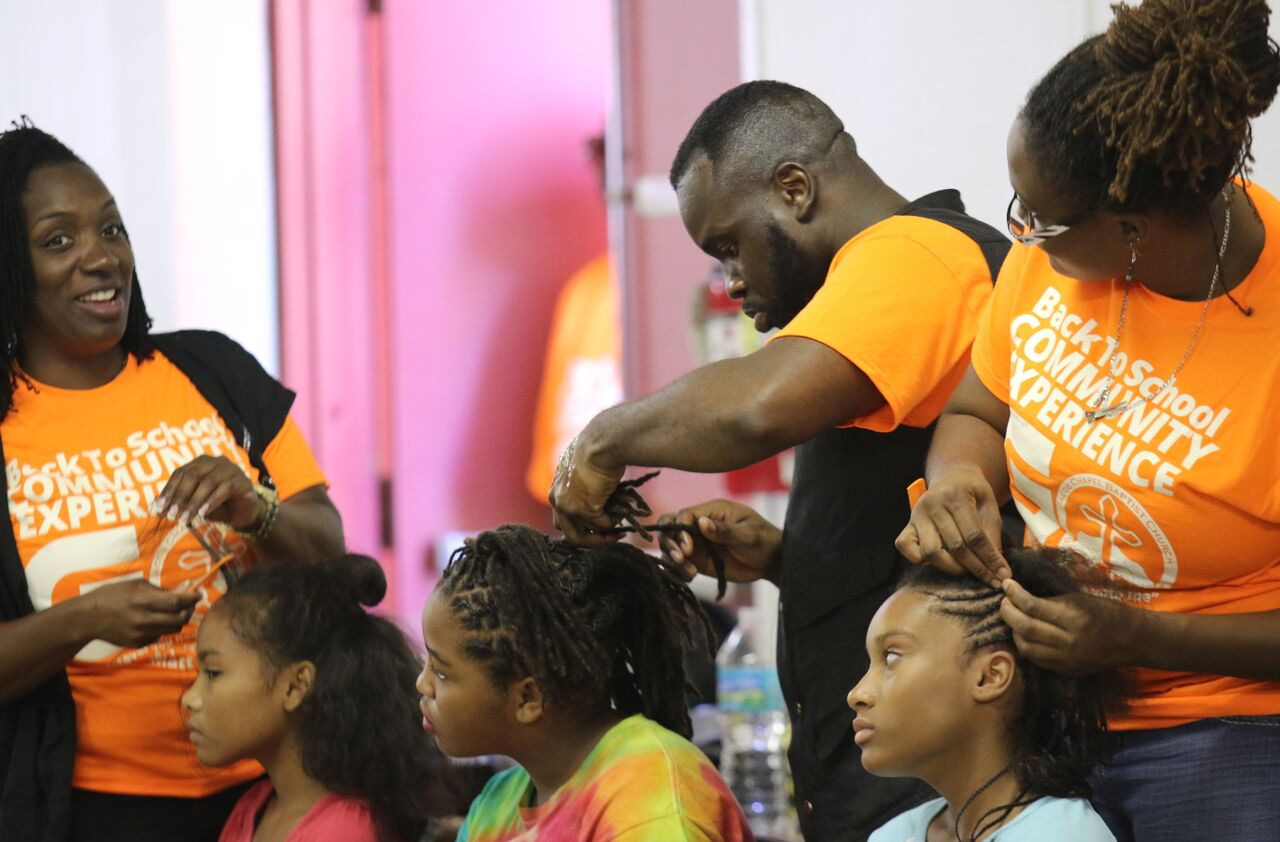 Hair stylists from Naturally U Braid Studio volunteer to braid the hair of local youth. Photos by Sheila Williams