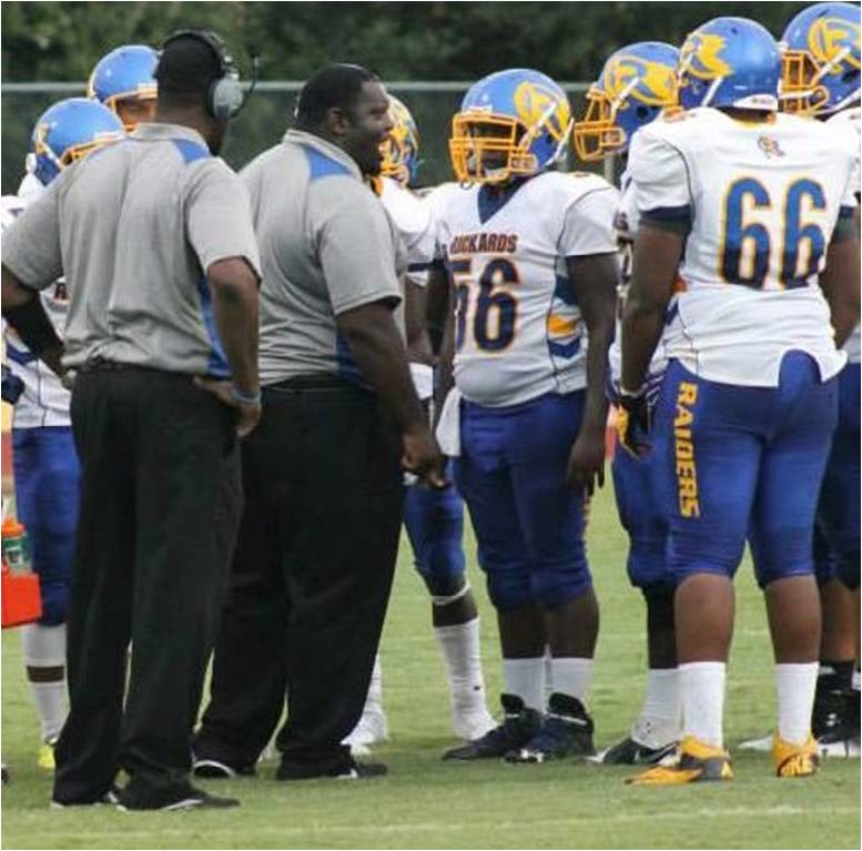 Coach Quintin Lewis, second from left, makes a point to his Rickards High School players during a game last season. Lewis is optimistic that the Raiders could end this season with a trip to the state tournament.  Photo by Idris Smith