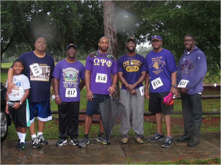 Members of Omega Psi Phi fraternity posed together for a finish line photo.
