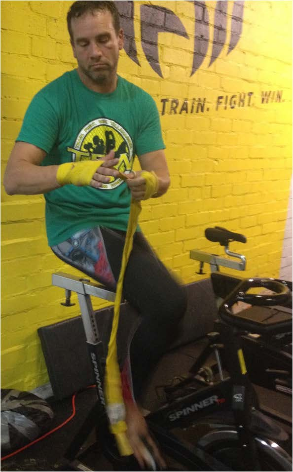 Bill Geiger wraps his hand as he begins a warm-up routine at Train. Fight. Win. gym where is preparing for a MMA fight.