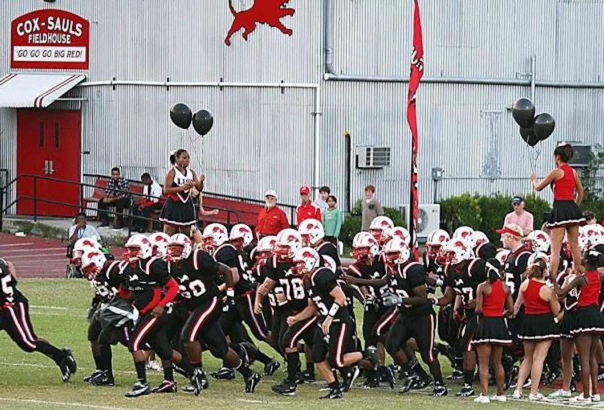 Leon High School football team prepared to play Chiles High school in this picture from 2009. In the background, is a photo of the Cox-Sauls fieldhouse named after Gene Cox and Jim Sauls. Photo Courtesy of Leon High School.