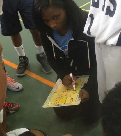 Coach Milan Clayton draws up a play for her Comets team during halftime of their game at Tooks Recreation Center on Saturday. Photo by St. Clair Murraine