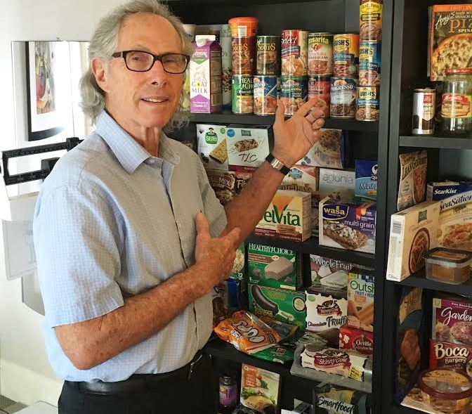 Standing in front of his shelf of healthy food alternatives, Dr. Freddy Kaye showcases the beans that can substitute for meat.  / Photo by Haylee Bell
