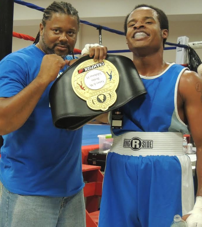 Bill Ishmael and Trainer Tyrese Williams celebrate after Ishmael's victory in his  amateur boxing debut at the National Guard Armory. Photo by Robyn Murrell