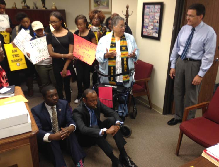 NAACP President/CEO Cornell William Brooks and NAACP Youth & College Division National Director Stephen Green occupy the lobby floor of the Roanoke district office of Congressman Bob Goodlatte. Goodlatte's Chief of Staff Pete Larkin looks on. Brooks was refusing to leave unless arrested or hearing from Goodlatte on his intent to hold a hearing on the Voting Rights Act. PHOTO: Courtesy/NAACP