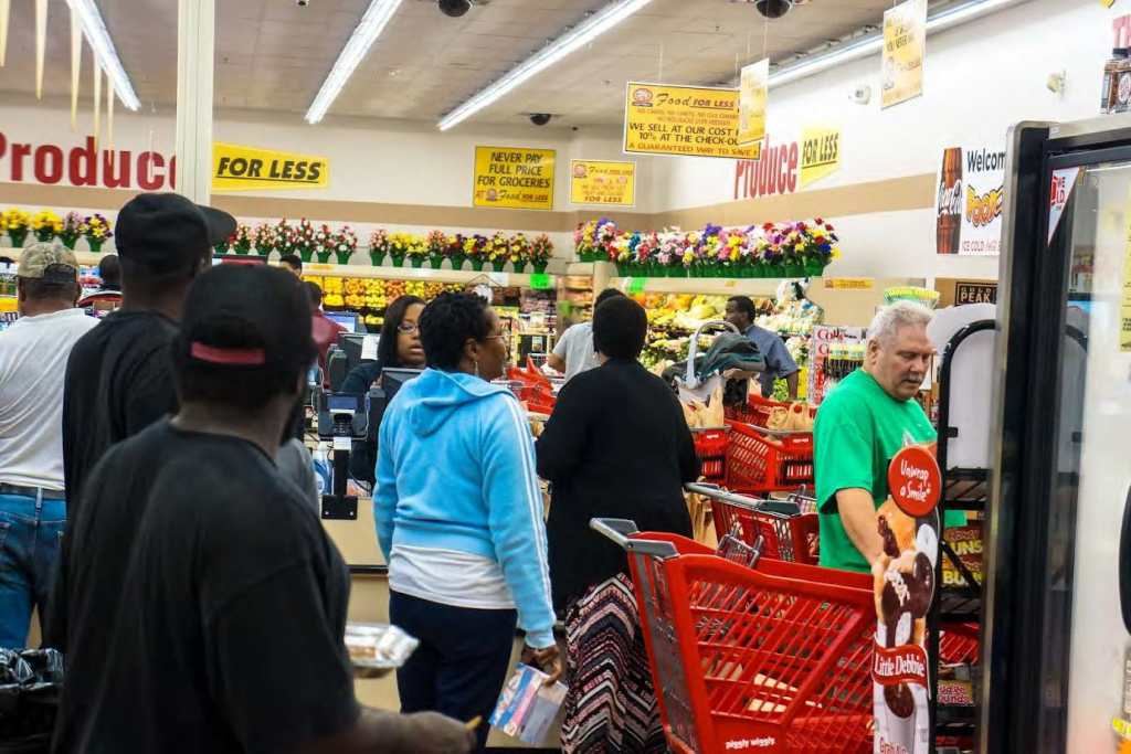 Piggly Wiggly shoppers in line being checked out by store employees. Photo by Elegance Davis